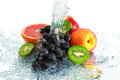 Fruit in a spray of water on white background Royalty Free Stock Photos