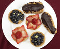 Fruit tarts and eclairs teatime treats of homemade filled with confectioner s custard topped with fresh strawberries or Stock Photos