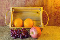 Fruits (apple, orange , grape )  in an wood box, on sack sisal background Royalty Free Stock Photo