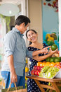 Fruits choosing vertical image of a senior couple in the grocery Royalty Free Stock Photos