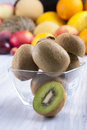 Fruits close up photo of edible a kiwi with other full colors in the background on a solid bright blue wooden table Stock Photo