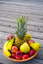 Fruits different in a bowl on wooden ground Stock Photography