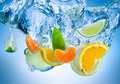 Fruits fall deeply under water with a big splash tropical Stock Image