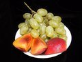 Fruits grape and pieces of peach in plate on black background Stock Images