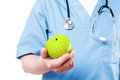Fruits make you healthy close up of surgeon in blue uniform holding green apple while standing isolated on white Stock Images