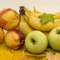 Fruits on maple leaves there are bananas ammples and nectarines Royalty Free Stock Image