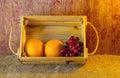 Fruits ( orange , grape )  in an wood box, on sack sisal background Royalty Free Stock Photo