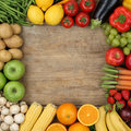 Fruits and vegetables forming a frame on a wooden board with cop Royalty Free Stock Photo