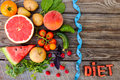 Fruits, vegetables and in measure tape in diet on wooden background. Royalty Free Stock Photo