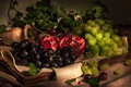 Fruits on vintage tray fresh green and black grapes and pomegranates with ceramic vase Royalty Free Stock Photos