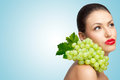 Fruity thoughts a thoughtful sexy lady with a bunch of healthy green grapes on her shoulder looking aside Royalty Free Stock Photo