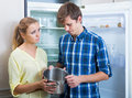 Frustraited starving female and man near fridge without any food young spanish men Stock Photos