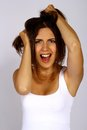 A frustrated and angry woman is screaming out loud pulling her hair Stock Photo