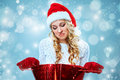 Frustrated and annoyed beautiful young woman in santa claus hat with a gift on a blue background Stock Photo