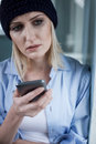 Frustrated blond female druggie is very lonely sad young woman has narcotic addiction she holding a mobile phone with frustration Stock Image