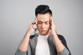 Frustrated business asian man with a headache - isolated over gr Royalty Free Stock Photo