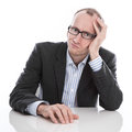 Frustrated businessman wearing glasses sitting at desk with head in hand isolated on white background Royalty Free Stock Photography