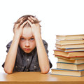 Frustrated child with learning difficulties portrait of upset schoolboy sitting at desk books holding his head Royalty Free Stock Photography
