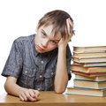 Frustrated child with learning difficulties portrait of upset schoolboy sitting at desk books holding his head Royalty Free Stock Photo