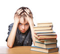 Frustrated child with learning difficulties portrait of upset schoolboy sitting at desk books holding his head Royalty Free Stock Images