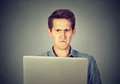 Frustrated disgusted man looking at laptop displeased Royalty Free Stock Photo