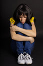 Frustrated girl sitting depressed on a black background Royalty Free Stock Photos
