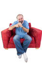 Frustrated man biting a remote control middle aged bearded sitting in red armchair from television set screwing up his eyes in Royalty Free Stock Images