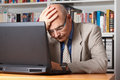 Frustrated man with laptop stressed and elderly in front of his Stock Photos