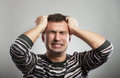 Frustrated man portrait of a screwing up his eyes gray background Royalty Free Stock Images