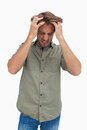 Frustrated man pulling his hair and looking down on white background Stock Image