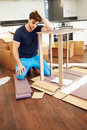 Frustrated man putting together self assembly furniture with hand on head Royalty Free Stock Photo