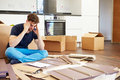 Frustrated man putting together self assembly furniture on his own with head in hands Royalty Free Stock Photography
