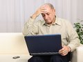 Frustrated mature man with laptop portrait of a desperate shocked business looking at at home Royalty Free Stock Image