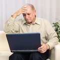 Frustrated mature man with laptop portrait of a desperate shocked business looking at at home Stock Photography