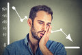 Frustrated stressed young man desperate with financial market chart graphic going down Royalty Free Stock Photo
