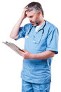 Frustrated surgeon mature in blue uniform holding hand in hair and looking at his clipboard while standing isolated on white Stock Photo