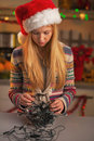 Frustrated teenage girl in santa hat untangling christmas lights kitchen Stock Photography