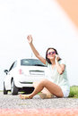 Frustrated woman hitchhiking while using cell phone by broken down car Royalty Free Stock Photo