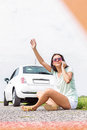 Frustrated woman hitchhiking while using cell phone on country road by broken down car Royalty Free Stock Photo
