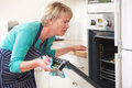 Frustrated woman looking in oven with disappointed expression frustration Royalty Free Stock Photos