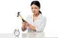 Frustrated woman smashing an alarm clock angry business with hammer Stock Photos