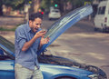 Frustrated young man calling roadside assistance after breaking down Royalty Free Stock Photo