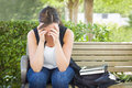 Frustrated young woman sitting alone on bench next to books upset with her head in her hands and backpack Stock Image