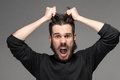 Frustration man tearing hair out in anger a black sweater portrait on gray background Stock Photo