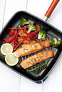 Frying pan with two salmon steaks and herbs Royalty Free Stock Photo