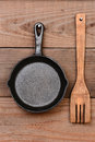Frying pan and wood fork closeup of a cast iron a wooden hanging on the wall of a rustic kitchen Stock Photography