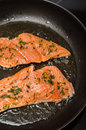 Frying salmon fish in a pan Royalty Free Stock Image