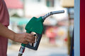 Fuel pipe in hand petrol station green Royalty Free Stock Image