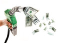 Fuel prices concept male hand holding green nozzle with dollars flying around Royalty Free Stock Photos