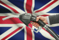 Fuel pump nozzle in hand with national flag on background - United Kingdom - UK - Great Britain